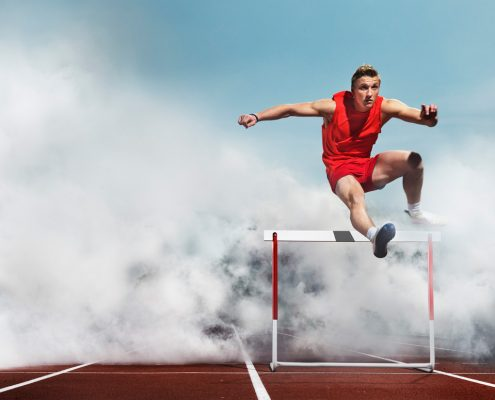 Runner Leaping a Hurdle With Large Dust Cloud Behind Him